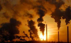 Smoke rises from chimneys of a factory during sunset in the Siberian town of Achinsk