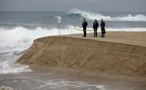 People watch as the Carmel River flows to the ocean at Carmel River State Beach on Monday, January 11, 2016.  County crews worked with equipment on Sunday to start the breach through the sand bar at the southern channel.  The river broke through on its own sometime Sunday night.  (Vern Fisher - Monterey Herald)